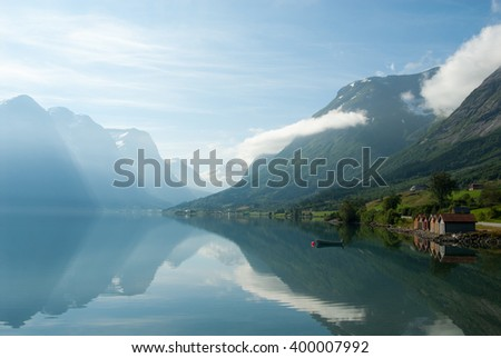 Landscape with mountains reflecting in the lake and small boat near the shore, Norway - stock photo