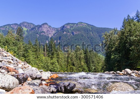 landscape with mountains trees and a river - stock photo