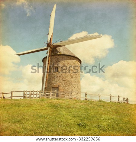 Landscape with old windmill in grunge and retro style. - stock photo