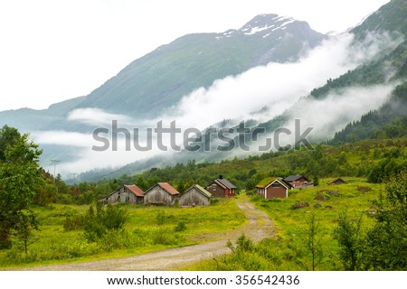 Landscape with old wooden houses and mountains covered by clouds, Norway - stock photo