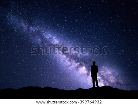 Landscape with purple Milky Way. Night sky with stars and silhouette of a happy man on the mountain. Beautiful Universe. Space background - stock photo