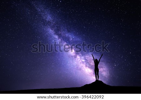 Landscape with purple Milky Way. Night sky with stars and silhouette of a standing sporty girl with raised-up arms on the stone - stock photo