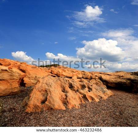 Landscape with red stones in desert under nice sky