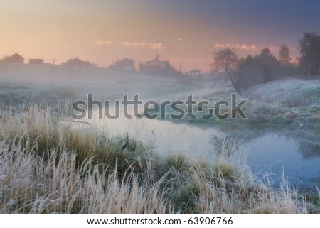 Landscape with river and frozen grass at misty sunny morning - stock photo
