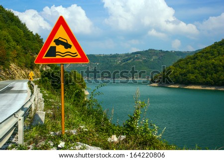 Landscape with Road Ends Sign beside the lake - stock photo
