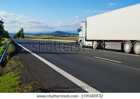 Landscape with road, the road goes white truck, in the distance a mountain and village - stock photo
