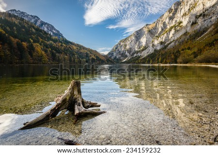 Landscape with root in lake water and mountains in background.Leopoldsteiner see,Styria,Austria.  - stock photo