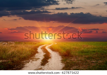 landscape with rut road on sunset sky background