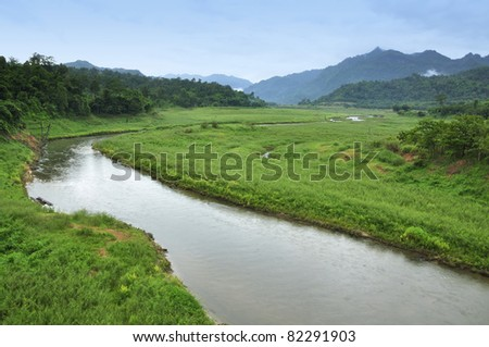 landscape with small river and green field - stock photo
