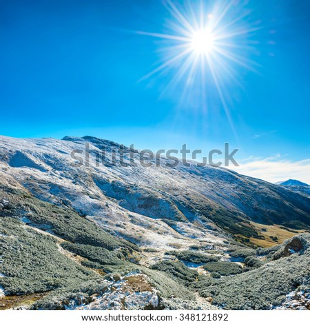 Landscape with snow in blue mountains over sun, sky and clouds - stock photo