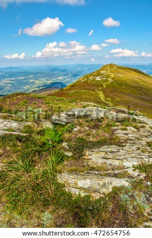 landscape with stones among the grass on the hillside near the path going to mountain top under a blue sky with clouds