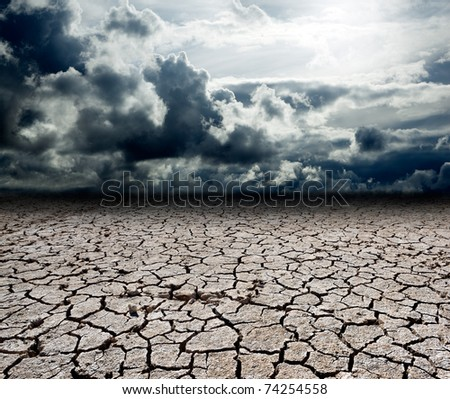 landscape with storm clouds and dry soil - stock photo