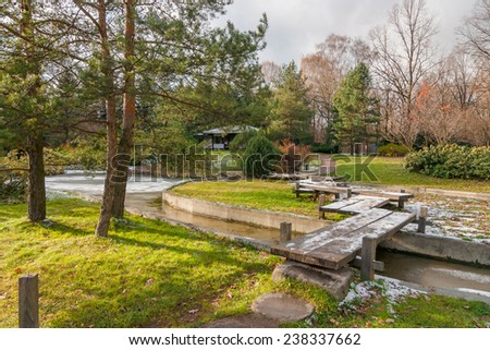 Landscape with the first snow in the autumn Japanese garden with a wooden bridge, pond and pavilion - stock photo