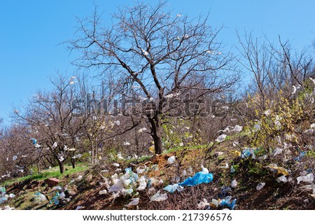 landscape with tree covered  plastic bags, garbage dump  - stock photo