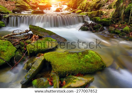Landscape with waterfall on mountain stream - stock photo