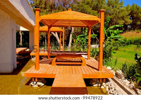 Landscape with wood pavilion for massage in tropical garden on summer resort - stock photo
