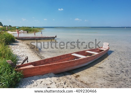 Landscape - wooden fishing boat, beach on the lake, reeds - stock photo