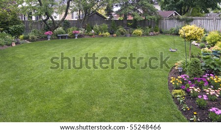 landscaped backyard surrounded by wooden fence - stock photo