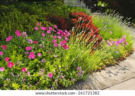 Landscaped garden at house with blooming flowers - stock photo