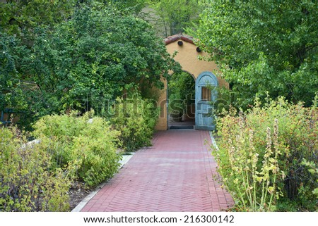 Landscaped garden with brick walkway and cottage looking doorway - stock photo
