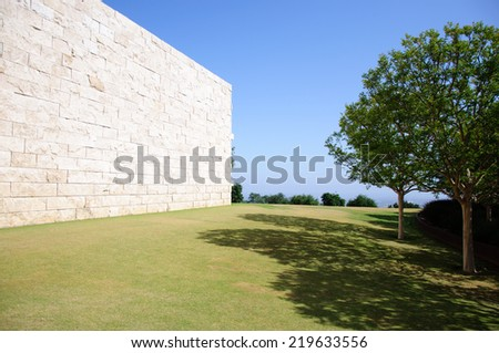 Landscaped Garden with Dining Tables Set in the Shade of Trees - stock photo