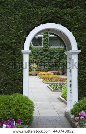 Landscaped garden with white pathway leading to flower beds - stock photo