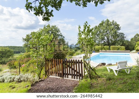 Landscaped pool in a country garden with wooden fence and distant views. Glimpses of sun appear through clouds. - stock photo