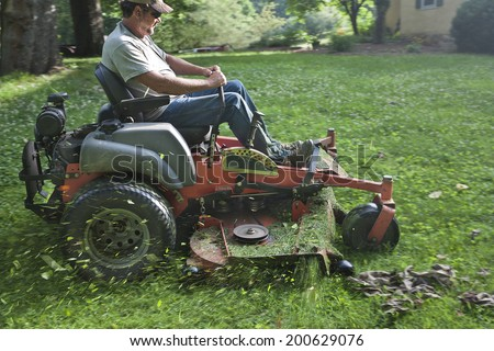 Landscaper cutting grass on riding lawn mower - stock photo