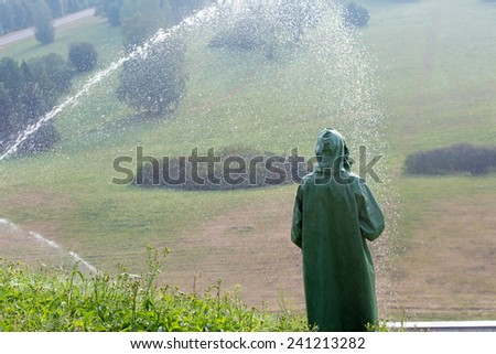Landscaper worker during watering green grass lawn with sprinkling tool