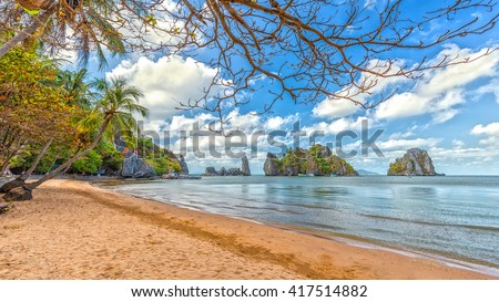 Landscapes coast with big rocks beautiful beach front cloudy blue sky, foreground tree overlooking beautiful bay, which attracts many tourists and recognized landscapes Vietnam national level