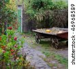 Landscaping design in a rustic style. Autumn garden and old Cart. - stock photo