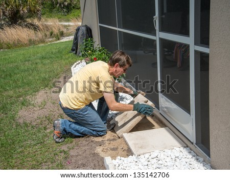 Landscaping Work - A man working outdoors.  He is placing heavy concrete patio slabs in the landscaping near the back door to the house. - stock photo