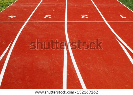 Lanes of a red race tracks with numbers for athletic venue - stock photo