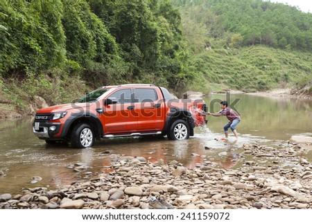 Lang Son, Viet Nam - Nov 4, 2014: Unidentified man washing his car (Ford Ranger Wildtrak) in river in Vietnam - stock photo