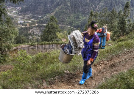 Langde Village, Guizhou, China - April 15, 2010: Chinese woman farmer peasant carries the weight on your shoulder. Asian female goes on a farm field with heavy supplies for processing plants. - stock photo