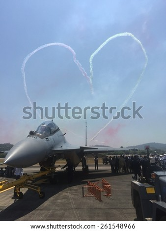 LANGKAWI - MARCH 17: A royal air force fighter jet readies against a heart shape aerobatic show at the Langkawi International Maritime and Aerospace (LIMA) exhibition in Langkawi March 17, 2015 - stock photo