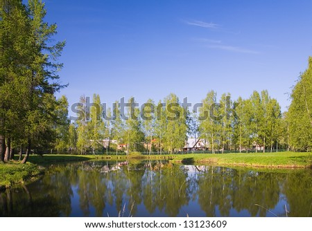lanscape with houses near lake under blue sky - stock photo