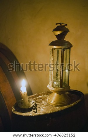 Lantern and candle, lukewarm light, vertical image
