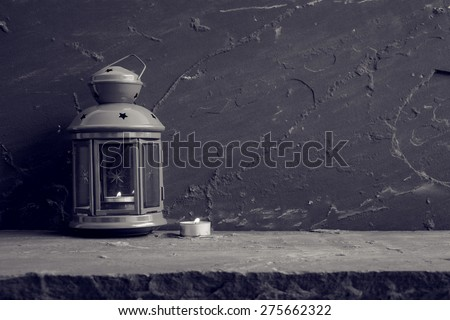 Lantern and candle on stone table over stone grunge background, black and white - stock photo
