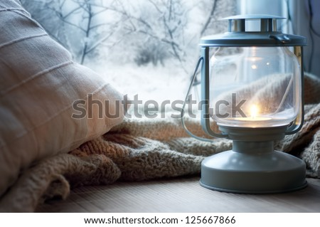 lantern and pillows on windowsill with winter view - stock photo