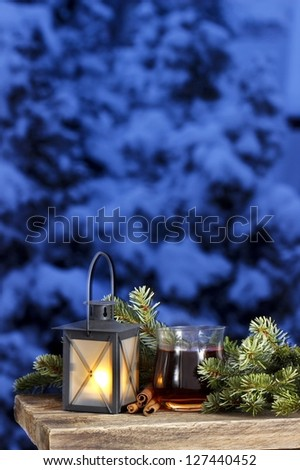 Lantern, glass of tea and fir with copy space - stock photo