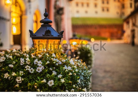 Lantern in the flowered on the table of street cafe in Krakow, Poland. - stock photo