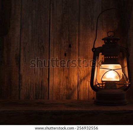 lantern lamp light dark wooden wall table background - stock photo