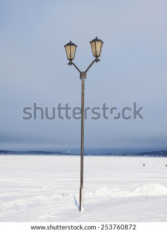 Lantern on the bank of lake in the winter  - stock photo