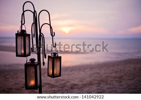 lantern on the beach in sunset - stock photo
