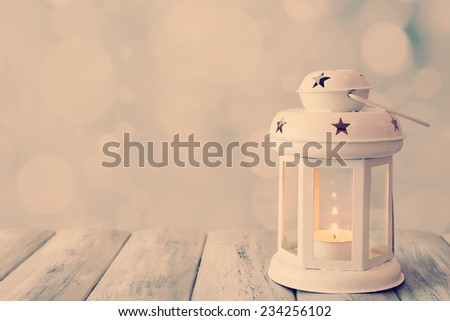 Lantern on wooden table on bright background - stock photo
