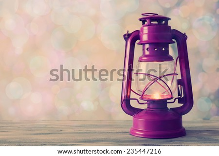 Lantern on wooden table on bright background