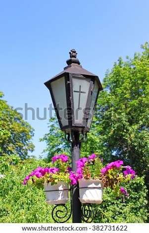 Lantern with a cross on the glass, near the church - stock photo