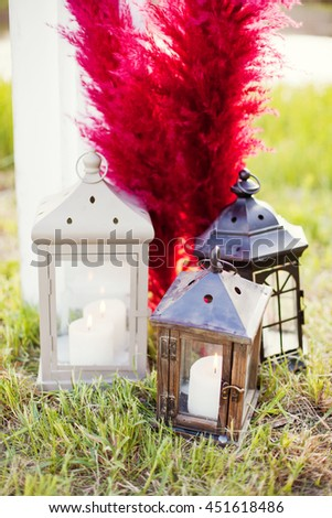 lantern with candle and red feather - stock photo