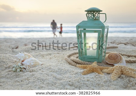 Lantern with shells on beach with soft focus father and son collecting shells in the background at sunrise - stock photo